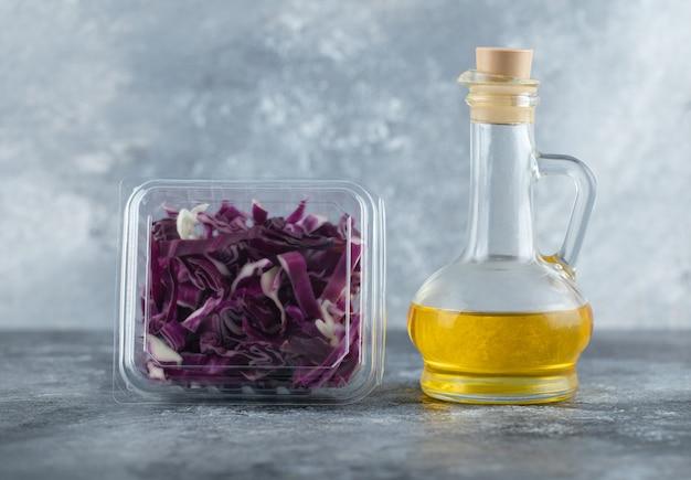Foto ravvicinata di cavolo viola tritato e bottiglia di olio d'oliva su sfondo grigio.