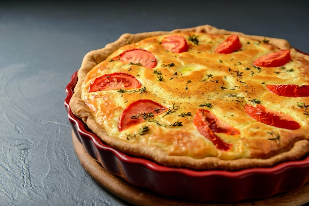 Close-up photo of classic quiche lorraine pie with tomatoes