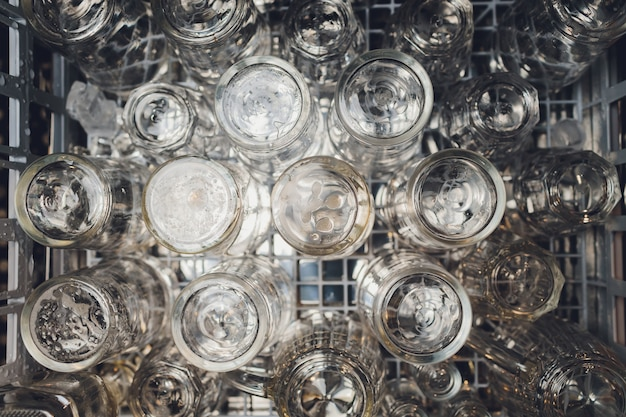 Close-up photo of clean washed and polished bar and pub glasses hanging over empty glasses