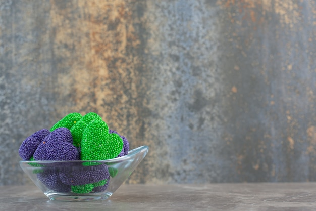 Close up foto di caramelle colorate in una ciotola di vetro su sfondo grigio.