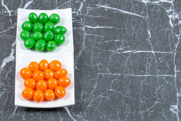 Close up photo of colorful candy balls on white plate.