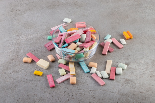 Close up photo of colorful gums in glass bowl over grey background.