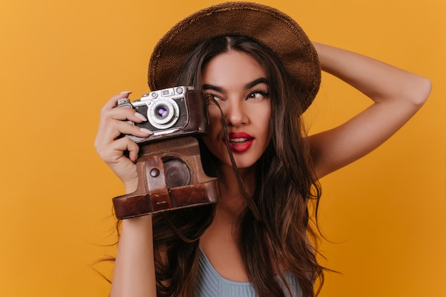 Close-up photo of concentrated female photographer with dark long hair