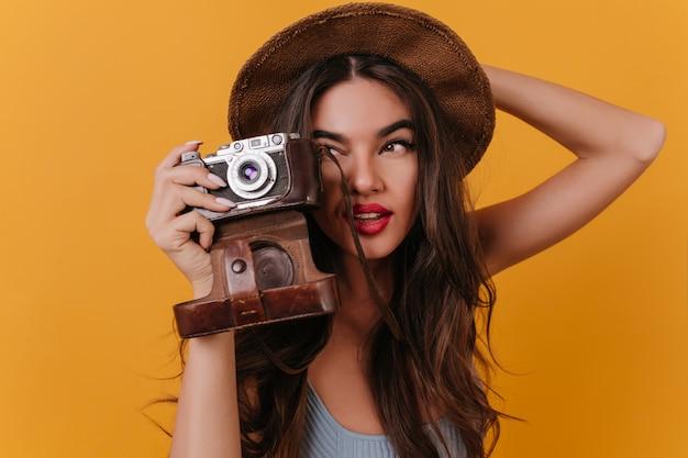 Foto del primo piano del fotografo femminile concentrato con capelli lunghi scuri