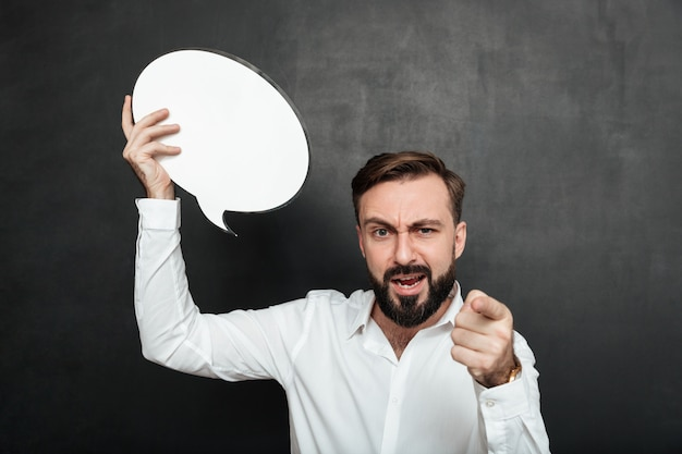Close up photo of confident strict man holding blank speech bubble and pointing index finger at camera over dark gray wall copy space