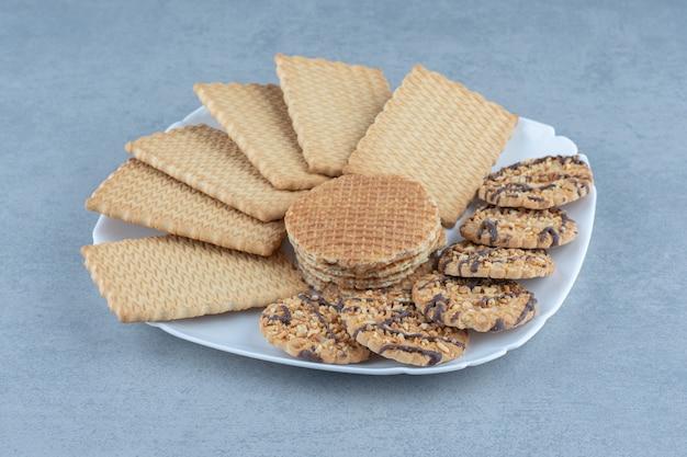 Chiuda sulla foto dei biscotti sulla zolla bianca. vari tipi di cookie