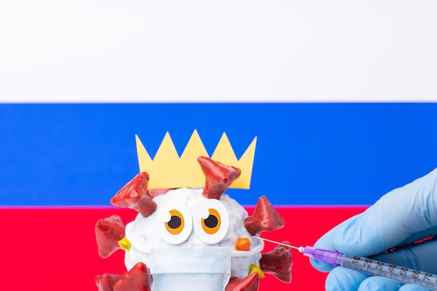 Close-up photo of covid-19 self-made cell with funny scared face, russian flag in the background
