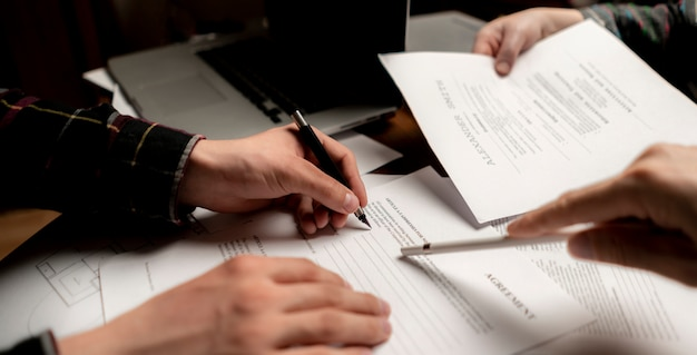 Close up photo of crew of businessmen signing documents