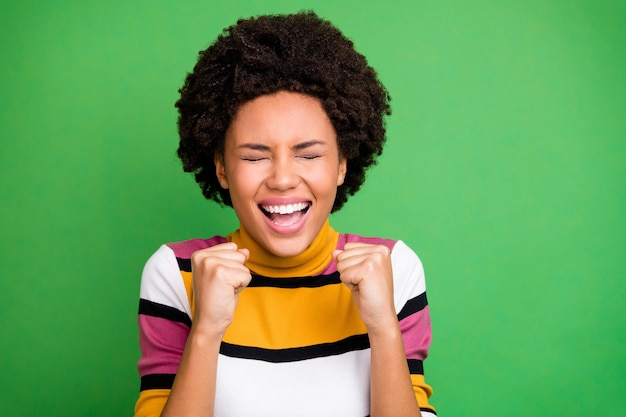 Close up photo of delighted crazy afro american girl celebrate champion lottery win feel rejoice emotions raise fists scream close eyes wear good look outfit
