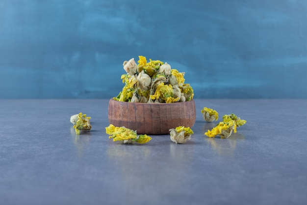 Close up photo of dried flowers in wooden bowl over grey.