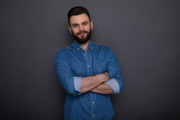 Close up photo of excited happy young modern bearded hipster man in jeans wear isolated