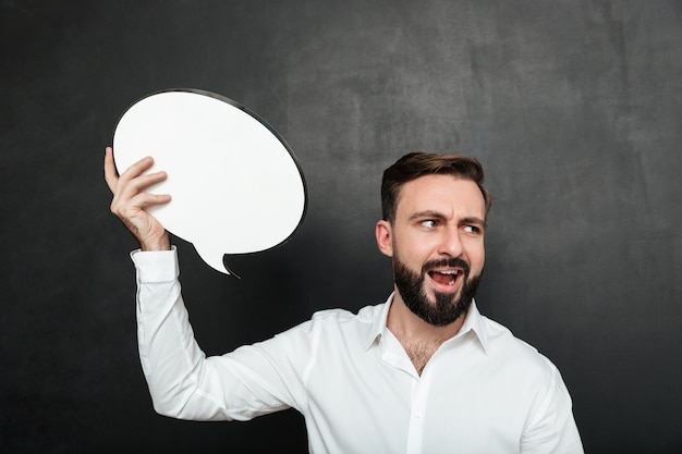 Close up photo of excited man holding blank speech bubble shouting and looking aside over dark gray wall copy space