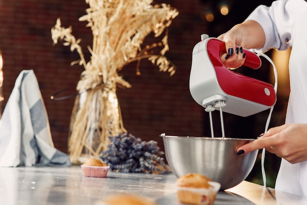 Close up photo of female confectioner mixes a fresh cream in deep metal plate with a red kitchen mixer.