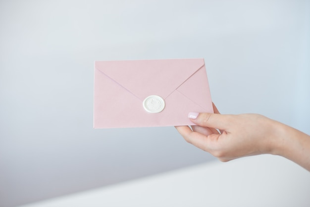 Close-up photo of female hands holding invitation envelope with a wax seal, gift certificate, postcard, wedding invitation card