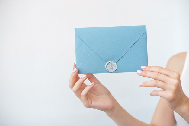 Close-up photo of female hands holding a silver blue invitation envelope with a wax seal, a gift certificate, a postcard, a wedding invitation card.
