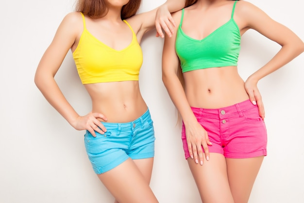 Close up photo of fit slim women's bellies with perfect skin
