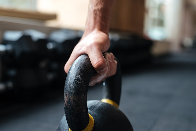 Close up photo of fitness hand and kettlebell. sideways