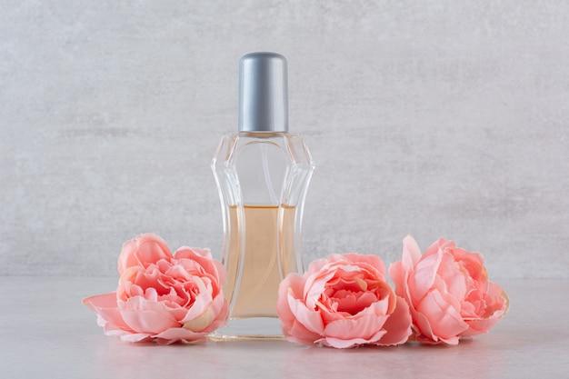 Close up foto della bottiglia di profumo con fiori.