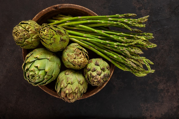 Close up photo of fresh artichoke in the old wooden bowl and bunch of green asparagus. top view on dark background.