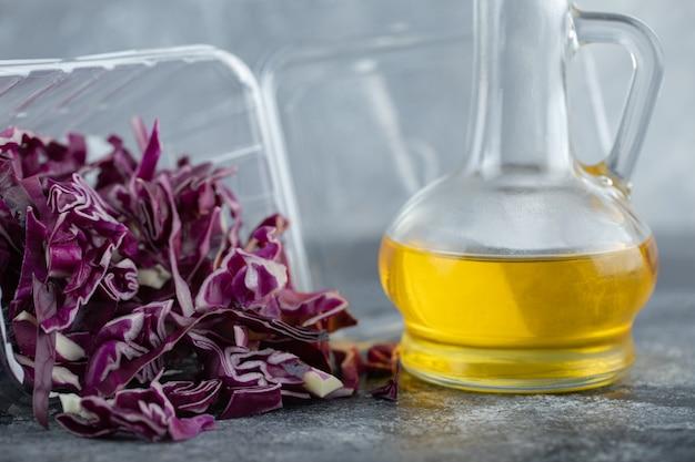 Foto ravvicinata di cavolo fresco tritato con una bottiglia di olio.
