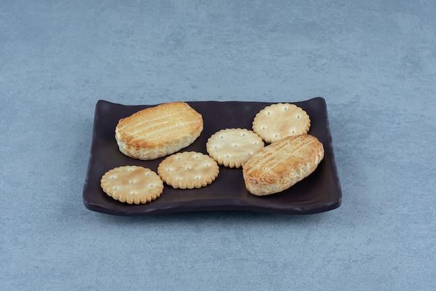 Chiuda sulla foto del piatto marrone dei biscotti freschi.