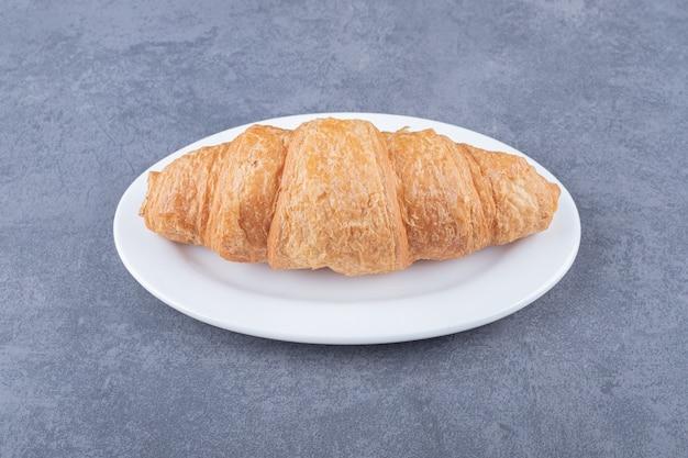 Chiuda sulla foto del croissant francese fresco sulla zolla bianca.