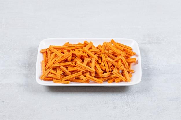 Primo piano foto di patatine fritte fresche sul piatto bianco.