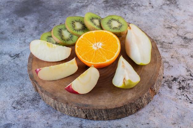 Primo piano foto di fette di frutta fresca su tavola di legno.
