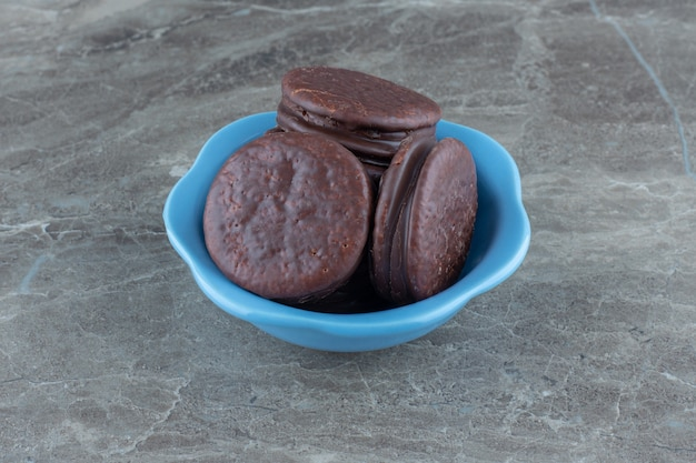 Foto ravvicinata di biscotti al cioccolato fatti in casa freschi sulla ciotola blu.
