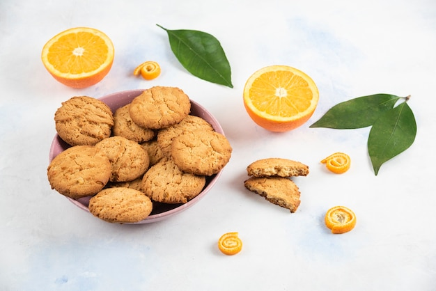 Close up photo fresh homemade cookies in bowl and organic oranges in ground with leaves.