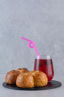 Primo piano foto di biscotti freschi fatti in casa con succo di frutta sul vassoio nero