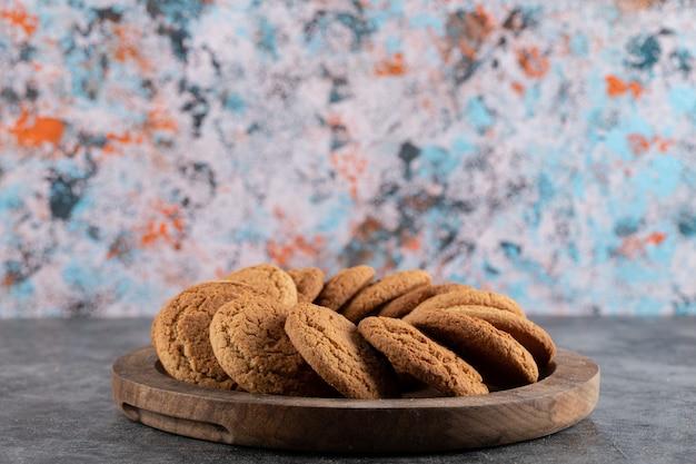 Foto ravvicinata di biscotti freschi fatti in casa sul vassoio in legno. spuntino delizioso.