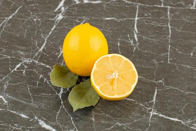 Close up photo of fresh lemons on grey.