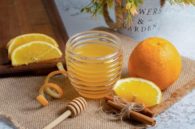 Close up photo of fresh orange with honey .