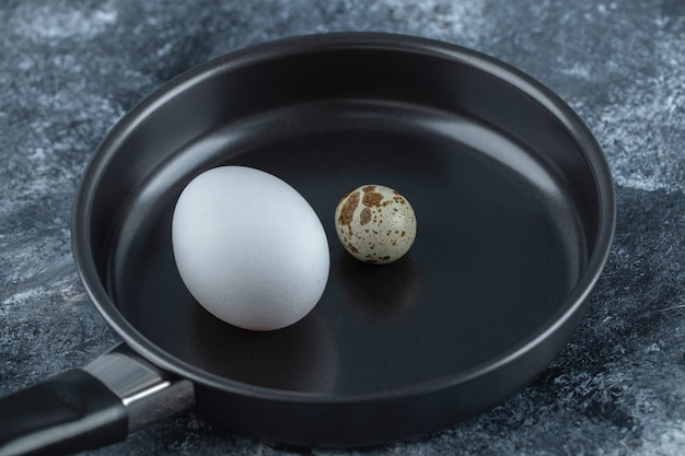 Close up photo of fresh organic chicken egg with quail eggs.