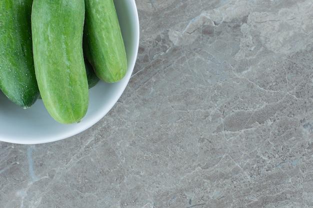 Chiuda sulla foto dei cetrioli organici freschi in ciotola bianca.