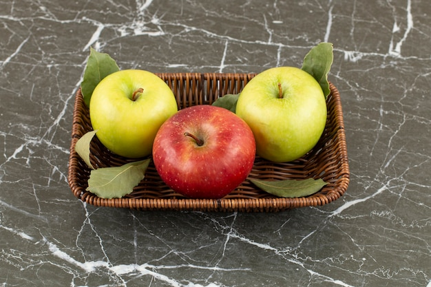 Close up photo of fresh organic red and green apples in bucket on grey.