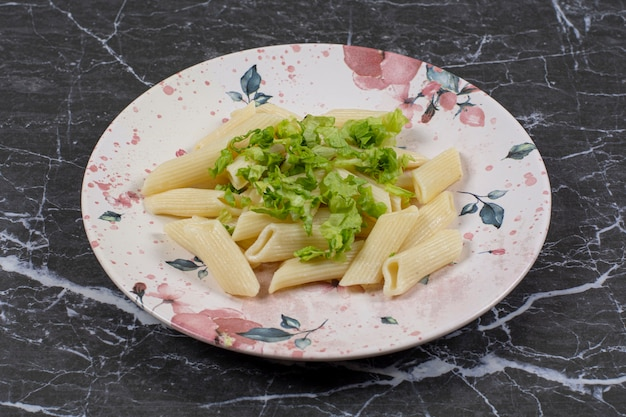 Close up photo of fresh penne pasta with greens.