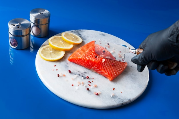 Close-up photo of fresh raw salmon, trout fillet on the marble cutting board with salt, pepper and lemon slices