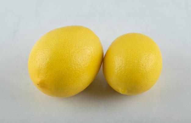 Крупным планом фото свежие спелые лимоны на белом фоне.