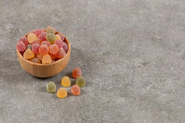Primo piano foto di marmellata dolce fresca nella ciotola di legno su grigio.