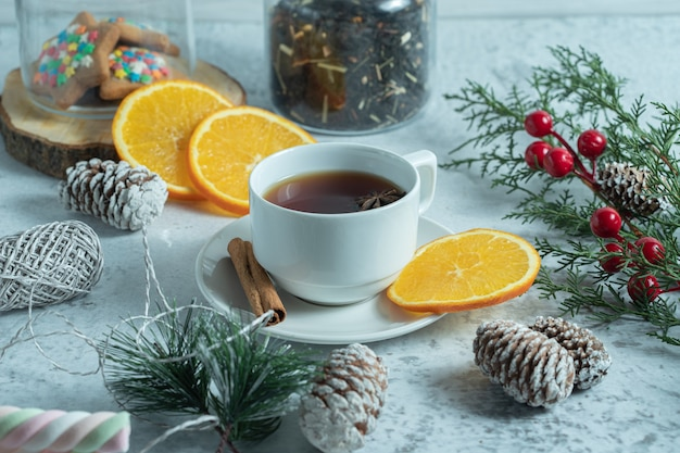 Close up photo of fresh tea with orange slices.