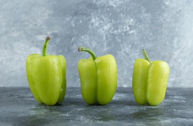 Close up foto di verdure fresche. peperoni verdi su sfondo grigio.