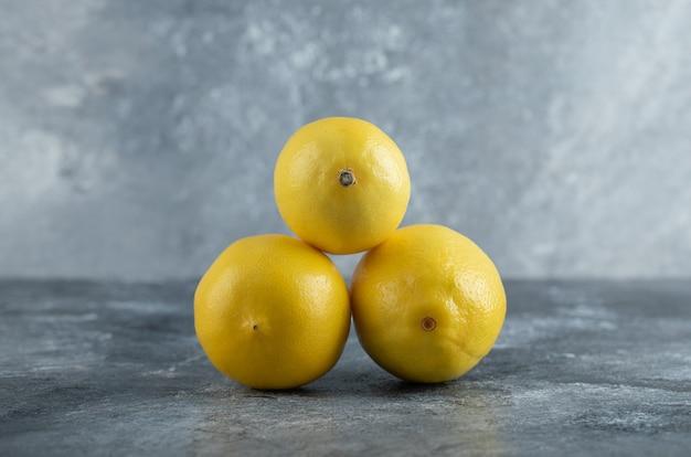Close up foto di freschi limoni gialli su sfondo grigio.