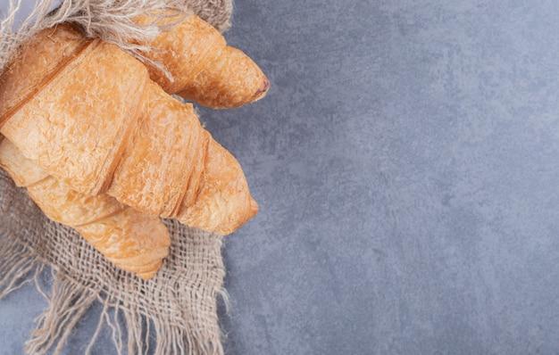 Close up foto di croissant appena sfornati su sfondo grigio.