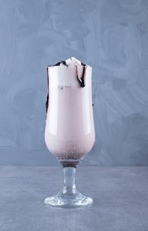 Close up foto di frullato di latte appena fatto al cioccolato su sfondo grigio.