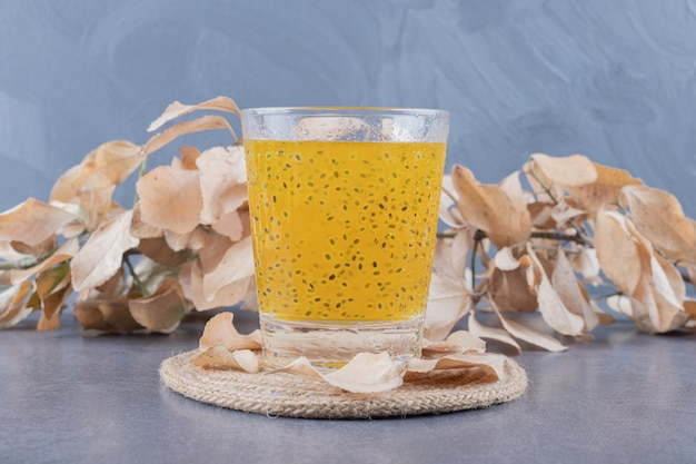 Close up photo of freshly made orange juice with decorative leaves on grey background.