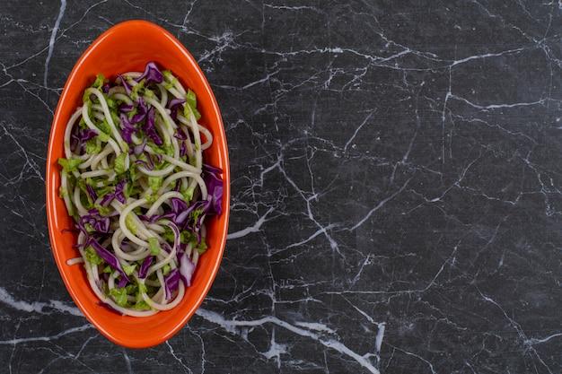 Primo piano foto di spaghetti appena fatti con salsa di verdure in una ciotola arancione.
