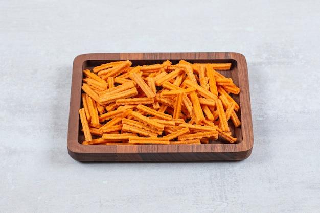Primo piano foto di patatine fritte sul piatto di legno.