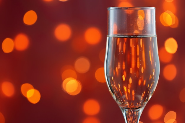 Close up photo of full champagne glass against blurred lights